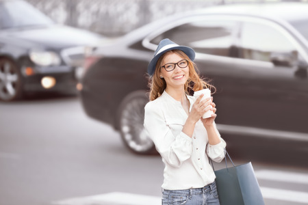 Happy young trendy student holding a coffee-to-go cup and standing at the crosswalk in an urban city. photo