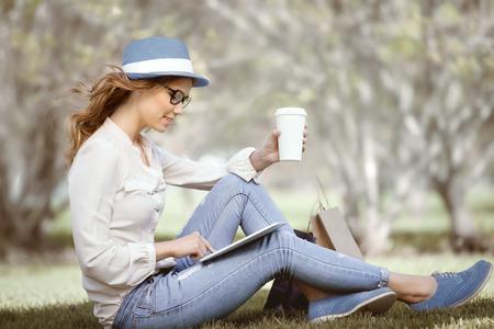 estilo urbano: Mujer joven feliz que una taza de caf� desechables sentado en la hierba y el uso de la almohadilla t�ctil en su tableta en un parque de verano.