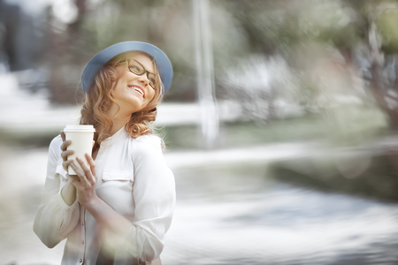 Happy young fashionable woman taking a coffee break after shopping, smiling with a coffee-to-go in her hands in a summer park. photo