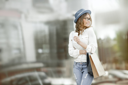 Happy young fashionable woman with bags having a coffee break after shopping and holding take away coffee against urban background. photo