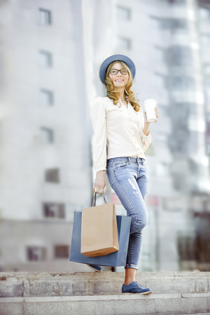 to go cup: Happy young trendy woman drinking take away coffee and walking down the stairs after shopping with bags in an urban city. Stock Photo