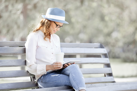 Happy young student with a tablet and a disposable coffee cup sitting on the bench and reading in a summer park. photo