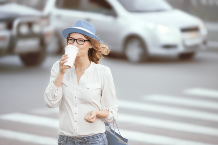 Happy young fashionable student drinking hot take away coffee and crossing a road against urban background. photo
