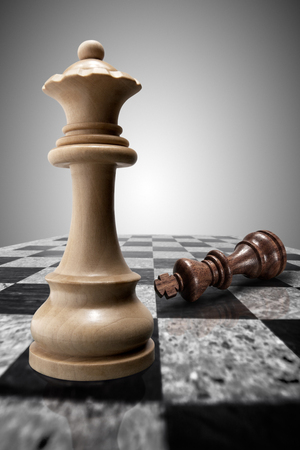chessboard: White wooden victorious queen standing on a chessboard against the background of a crushed defeated king. Stock Photo