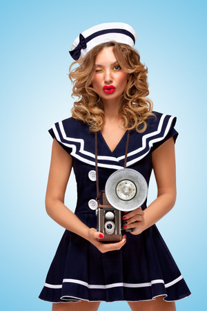 sailor girl: Retro photo of a fashionable pin-up sailor girl with an old vintage photo camera with bulb flash winking to the camera on blue background. Stock Photo