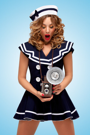Retro photo of a fashionable pin-up sailor girl looking surprisingly at an old vintage photo camera with bulb flash on blue background.