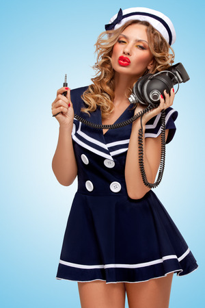 unplugged: Retro photo of a fashionable pin-up sailor girl with big vintage unplugged music headphones on blue background.