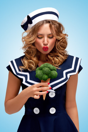 Creative retro photo of a fashionable pin-up sailor girl looking surprised with a broccoli ice cream in a waffle cone on blue background. photo