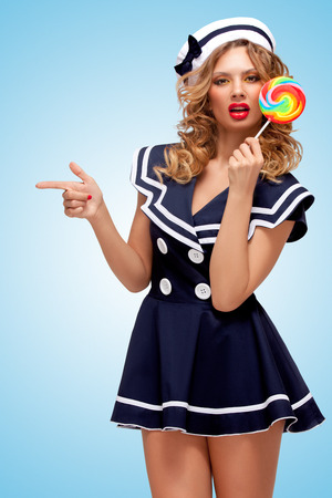 Creative photo of a playful pin-up sailor girl with a colorful lollipop, pointing aside with a finger on blue background. photo