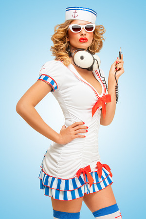 unplugged: Retro photo of a fashionable pin-up sailor girl in sunglasses with big vintage unplugged music headphones on blue background. Stock Photo