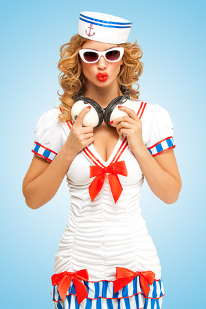 Retro photo of a fashionable pin-up sailor girl in sunglasses with duck lips, holding big vintage music headphones around her neck on blue background. Reklamní fotografie