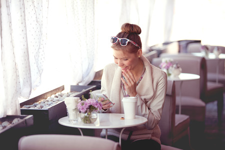 Photo of a beautiful happy young woman using wireless internet, surfing the net via smartphone and drinking coffee in a cafe in the morning. photo