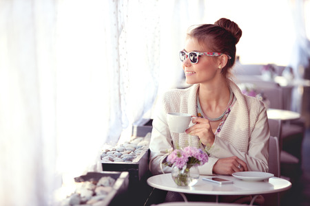 Photo of a beautiful happy young woman with smartphone and sunglasses, drinking hot tea or coffee on a cafe patio and looking out the window. 免版税图像
