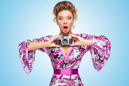 taking photograph: Retro photo of an amazed fashionable hippie homemaker, holding an old vintage photo camera with two hands and showing emotions on blue background.