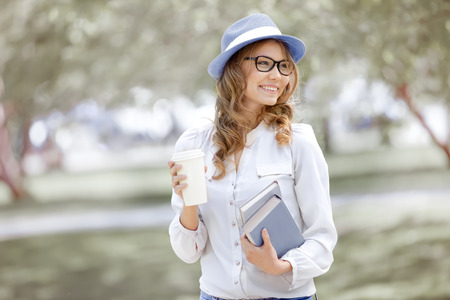 women glasses: Happy young woman with a coffee-to-go, walking in a summer park and holding books for reading. Stock Photo