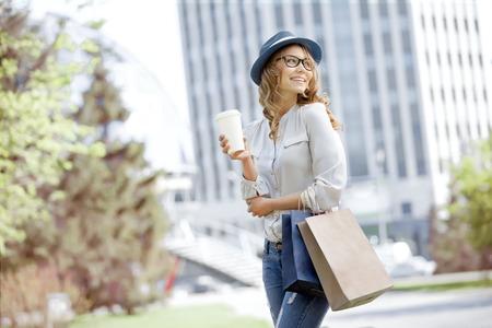 Gelukkig jonge trendy vrouw nemen opslag koffie drinken en lopen met boodschappentassen na het winkelen in een stedelijke stad.