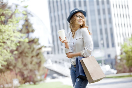 stylish girl: Happy young trendy woman drinking take away coffee and walking with shopping bags after shopping in an urban city.