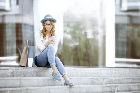 使い捨てのコーヒー カップおよび買い物袋、階段の上に座って、夏の公園での wi-fi インターネット経由での通信のため彼女のスマート フォンを使 写真素材