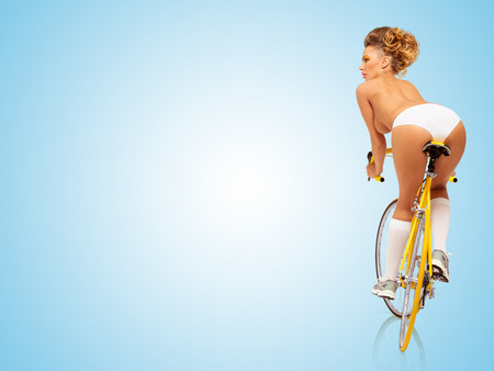 Retro photo of a nude sexy pin-up girl in white panties riding a yellow racing bicycle on blue background. Stockfoto