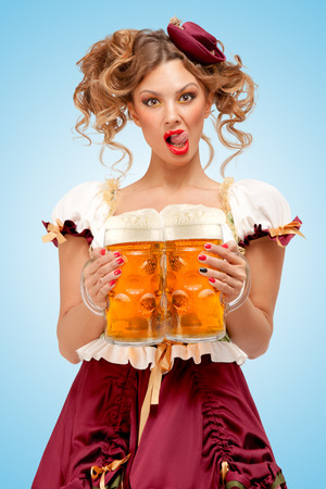 Young sexy Oktoberfest waitress, wearing a traditional Bavarian dress dirndl, serving two big beer mugs in a tavern and licking her lips on blue background.