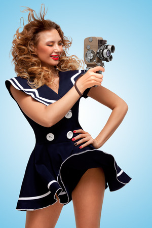 sailor girl: Retro photo of a glamorous pin-up sailor girl with an old vintage cinema 8 mm camera, standing in the wind, shooting a movie on blue background. Stock Photo