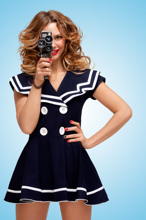 Retro photo of a glamorous pin-up sailor girl with an old vintage cinema 8 mm camera, looking like a sexy producer, shooting a movie on blue background. photo