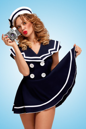sailor girl: Retro photo of a glamorous pin-up sailor girl with an old vintage photo camera showing emotions on blue background.