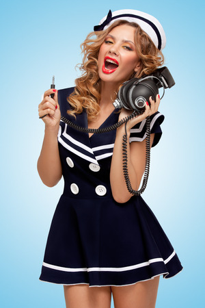 sailor girl: Retro photo of a fashionable pin-up sailor girl with big vintage unplugged music headphones on blue background.