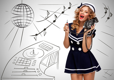 70s adult: Colorful photo of a clubbing fashionable pin-up sailor girl at the nightclub with big vintage unplugged music headphones on grey sketchy background of a DJ mixer and disco ball. Stock Photo