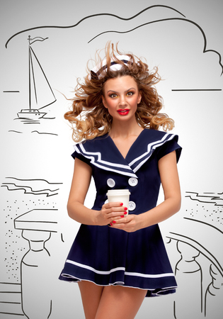 sailor girl: Creative photo of a beautiful pin-up sailor girl with a coffee-to-go cup, having wind in her hair on grey sketchy background. Stock Photo
