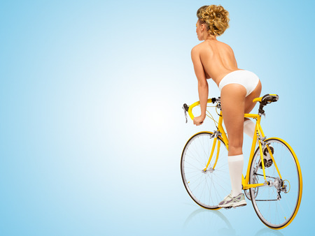 nude: Retro photo of a nude sexy pin-up girl in white panties riding a yellow racing bicycle on blue background. Stock Photo