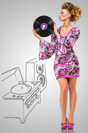 70s adult: Colorful photo of a clubbing fashionable hippie homemaker sending a kiss to a retro vinyl record in her hands on grey sketchy background of a DJ mixer and acoustic system. Stock Photo