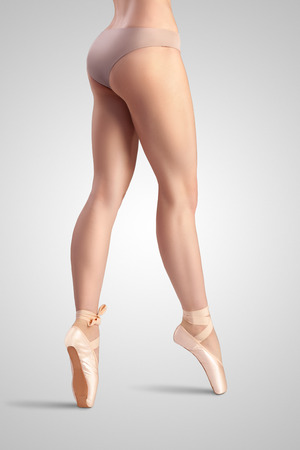 A graceful female classical ballet dancer on pointe shoes wearing beige satin underwear and standing on toes on a neutral light studio background.