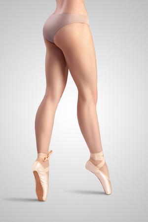 ballet slippers: Una bailarina de ballet agraciado femenina cl�sica en zapatillas de punta que usan ropa interior de sat�n beige y de pie sobre los dedos del pie en un estudio de fondo luz neutra.