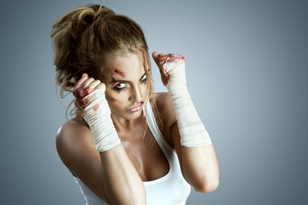 blood sport: Aggressive female fighter with bruises wearing bloody bandage on her fists, standing in boxing defense position, ready to fight on a neutral grey studio background.