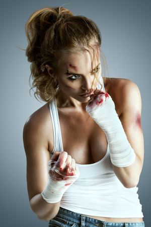 Aggressive female fighter with bruises wearing bloody bandage on her fists, standing in boxing defense position, ready to fight on a neutral grey studio background. photo