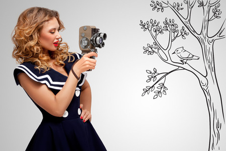 filming: Glamorous pin-up sailor girl filming nature and wildlife with an old retro cinema 8 mm camera, standing in front of a bird on grey sketchy background.