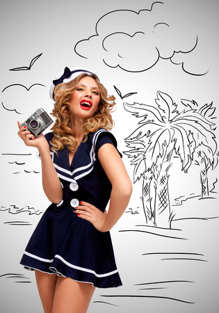 sailor girl: Retro photo of a glamorous pin-up sailor girl posing and taking a photo of a seashore and palm trees with an old vintage photo camera on grey sketchy background.