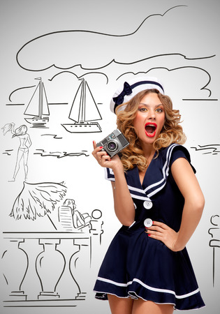 sailor girl: Retro photo of a glamorous pin-up sailor girl posing and taking a photo of a seashore and tourists with an old vintage photo camera on grey sketchy background. Stock Photo