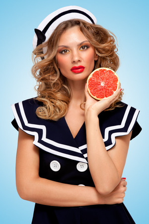 enzymes: Beautiful young woman in a sailor dress holding a red grapefruit, anti-aging organic skincare treatment for body and face on blue background.