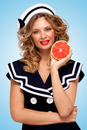 antiaging: Beautiful young woman in a sailor dress holding a red grapefruit, anti-aging organic skincare treatment for body and face on blue background.
