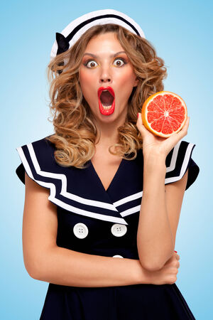 Beautiful amazed young woman with shocked face in a sailor dress holding a red grapefruit, anti-aging organic skincare treatment for body and face on blue background.