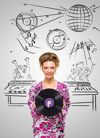 party system: Colorful photo of a clubbing fashionable hippie deejay at the dancing party holding a retro vinyl record in her hands on grey sketchy background of a DJ mixer.