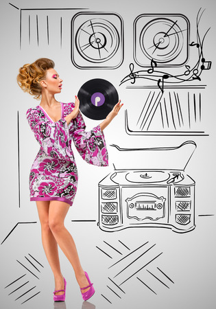70s adult: Colorful photo of a fashionable hippie homemaker holding a purple LP microgroove vinyl record in her hands on grey sketchy background of a vintage record player and vinyl collection. Stock Photo