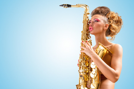 Retro photo of a sleepy nude pin-up woman with closed vintage winged eyes, hugging a saxophone like a tender lover on blue background.