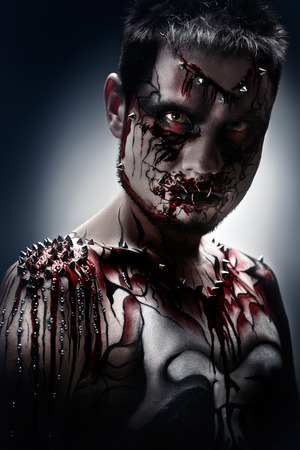 necromancer: A creepy portrait of a pierced halloween moor with bloody body art.