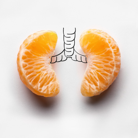 illness: A health concept of unhealthy human lungs of a smoker with lung cancer in dark shadows, made of mandarin segments. Stock Photo