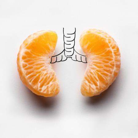 Een gezondheid concept ongezonde menselijke longen van een roker met longkanker in donkere schaduwen, gemaakt van mandarijn segmenten.