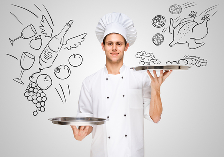 Sexy young waiter in a restaurant serving silver trays with sketchy food and drinks to customers for business lunch. Stock Photo