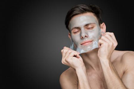 Portrait d'une belle jeune homme décoller un masque, le visage et soins de la peau du corps retraite visage. Banque d'images - 37104534